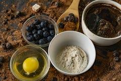 τοπ άποψη των συστατικών για το μαγείρεμα ή το ψήσιμο της σοκολάτας στον πίνακα, το βακκίνιο, το αυγό, το αλεύρι, το κακάο και τι στοκ φωτογραφίες