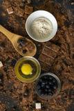 τοπ άποψη των συστατικών για το μαγείρεμα ή το ψήσιμο της σοκολάτας στον πίνακα, το βακκίνιο, το αυγό, το αλεύρι, το κακάο και τι στοκ εικόνες