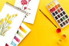 Τοπ άποψη των σχεδίων των λουλουδιών, των χρωμάτων, της βούρτσας και των ζωηρόχρωμων brushstrokes σε χαρτί για κίτρινο Στοκ φωτογραφίες με δικαίωμα ελεύθερης χρήσης