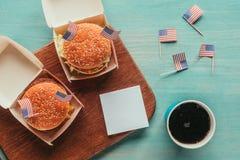 Τοπ άποψη των τακτοποιημένων burgers και του ποτού σόδας με τις αμερικανικές σημαίες ξύλινο tabletop Στοκ Εικόνες