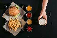 τοπ άποψη των τηγανιτών πατατών με εύγευστο burger στο δίσκο, τις ανάμεικτα σάλτσες και το ποτήρι εκμετάλλευσης χεριών της μπύρας Στοκ Φωτογραφίες