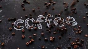 Τοπ άποψη των φασολιών ενός καφέ που αφορούν το μαύρο πίνακα Γράφοντας καφές κιμωλίας φιλμ μικρού μήκους