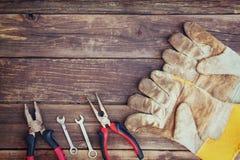 Τοπ άποψη των φορεμένων γαντιών εργασίας και των ανάμεικτων εργαλείων εργασίας πέρα από το ξύλινο υπόβαθρο Στοκ φωτογραφίες με δικαίωμα ελεύθερης χρήσης