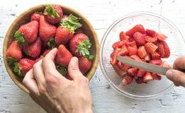 Τοπ άποψη των χεριών ατόμων ` s που προετοιμάζουν τη σαλάτα φρούτων με τις φράουλες Στοκ Φωτογραφίες