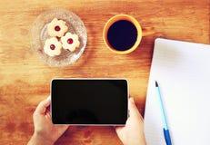 Τοπ άποψη των χεριών γυναικών που κρατά τη συσκευή ταμπλετών με την κενή οθόνη, με τα μπισκότα και το φλυτζάνι καφέ η εικόνα είνα Στοκ Εικόνα