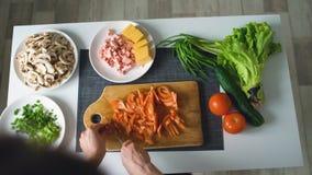 Τοπ άποψη των χεριών γυναικών που κόβει τα λαχανικά σε έναν ξύλινο πίνακα για το γεύμα πιτσών στην κουζίνα στο σπίτι Στοκ Εικόνες