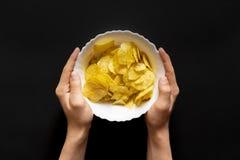 Τοπ άποψη των χεριών που κρατά ένα άσπρο πιάτο με τα πρόχειρα φαγητά φ τσιπ στοκ εικόνα