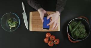 Τοπ άποψη των χεριών που τυλίγουν την τηλεφωνική οθόνη Χέρια που κρατούν το τηλέφωνο επάνω από τον πίνακα και τα τρόφιμα κοπής απόθεμα βίντεο