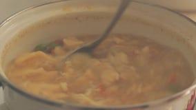 Τοπ άποψη, φυτική χορτοφάγος σούπα που βράζει και που σωριάζεται σε ένα τηγάνι χάλυβα, που ανακατώνει με ένα κουτάλι μαγειρεύοντα φιλμ μικρού μήκους