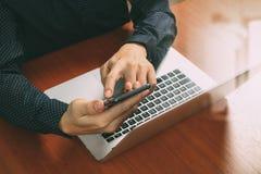 τοπ άποψη, χέρι επιχειρησιακών ατόμων που χρησιμοποιεί το έξυπνο τηλέφωνο, lap-top, σε απευθείας σύνδεση τράπεζα Στοκ εικόνες με δικαίωμα ελεύθερης χρήσης