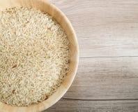 Τοπ άποψη - χονδροειδές ρύζι στο ξύλινο πιάτο και στο ξύλινο υπόβαθρο στοκ εικόνα