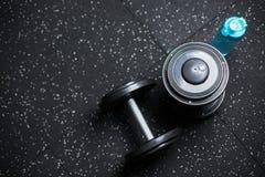 Τοπ άποψη δύο αλτήρων μετάλλων και ενός μπουκαλιού για το νερό, εξοπλισμός για την αθλητική ρουτίνα βάρους σε ένα θολωμένο υπόβαθ Στοκ φωτογραφία με δικαίωμα ελεύθερης χρήσης