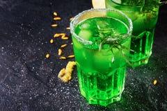 Τοπ άποψη δύο τεράστιων ποτηριών των μη οινοπνευματούχων ποτών με τα φύλλα πάγου και τραχουριού σε ένα μαύρο υπόβαθρο Στοκ Φωτογραφία