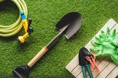 τοπ άποψη hosepipe, των προστατευτικών γαντιών και των εργαλείων κηπουρικής στη χλόη στοκ εικόνες