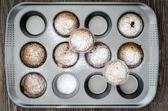 Τοπ άποψη muffins που ψεκάζονται με την κονιοποιημένη ζάχαρη στο πιάτο ψησίματος Στοκ Φωτογραφίες