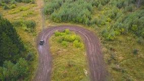 Τοπ άποψη SUV συνδετήρας Οι αθλητικές SUV στροφές αισθητά επάνω ανοίγουν την πλαϊνή βρώμικη διαδρομή Πλαϊνός αγώνας στη δασική πε φιλμ μικρού μήκους