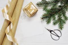 Τοπ έγγραφο συσκευασίας άποψης ντεκόρ Χριστουγέννων προτύπων και χρυσά κορδέλλα και ψαλίδι δώρων, flatlay σε ένα άσπρο ξύλινο υπό Στοκ Εικόνες