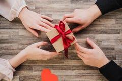 Τοπ, αρσενικών και θηλυκών χέρια άποψης, κιβωτίων δώρων, καρδιά του βαλεντίνου, στο υπόβαθρο του πίνακα στοκ εικόνα