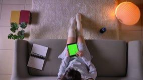 Τοπ βλαστός κινηματογραφήσεων σε πρώτο πλάνο της νέας ελκυστικής θηλυκής δακτυλογράφησης στην ταμπλέτα με την πράσινη συνεδρίαση  απόθεμα βίντεο