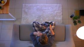 Τοπ βλαστός κινηματογραφήσεων σε πρώτο πλάνο του νέου αρσενικού που έχει μια τηλεοπτική κλήση στην ταμπλέτα καθμένος στον καναπέ  απόθεμα βίντεο