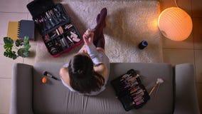 Τοπ βλαστός κινηματογραφήσεων σε πρώτο πλάνο του νέου ελκυστικού θηλυκού που εφαρμόζει μια συνεδρίαση makeup στον καναπέ στις χαρ απόθεμα βίντεο