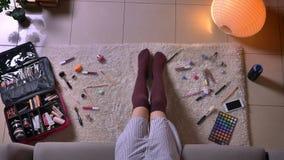 Τοπ βλαστός κινηματογραφήσεων σε πρώτο πλάνο του νέου ελκυστικού θηλυκού που εφαρμόζει μια συνεδρίαση makeup στο πάτωμα στις χαρι φιλμ μικρού μήκους