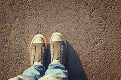 Τοπ εικόνα άποψης του προσώπου με τα παπούτσια πέρα από το δρόμο ασφάλτου Στοκ Εικόνες