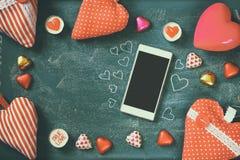 Τοπ εικόνα άποψης του smartphone, ζωηρόχρωμες σοκολάτες μορφής καρδιών, καρδιές υφάσματος στο υπόβαθρο πινάκων Εορτασμός ημέρας β Στοκ Εικόνες