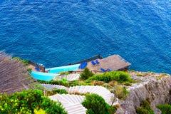 Τοπ εναέρια άποψη στην παραλία με τους υψηλούς απότομους βράχους και την αποβάθρα με Στοκ Εικόνες