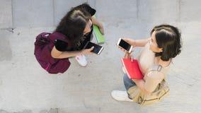 Τοπ εναέριο έξυπνο τηλέφωνο συζήτησης και χρήσης κοριτσιών εφήβων άποψης στο pedestria Στοκ Εικόνες