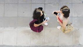 Τοπ εναέριο έξυπνο τηλέφωνο συζήτησης και χρήσης κοριτσιών εφήβων άποψης στο pedestria Στοκ φωτογραφία με δικαίωμα ελεύθερης χρήσης