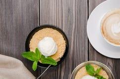 Τοπ επιδόρπιο θίχουλων της Apple άποψης με το παγωτό βανίλιας, πράσινη μέντα στον γκρίζο ξύλινο πίνακα Cappuccino φλιτζανιών του  Στοκ εικόνα με δικαίωμα ελεύθερης χρήσης