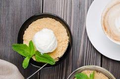 Τοπ επιδόρπιο θίχουλων της Apple άποψης με το παγωτό βανίλιας, πράσινη μέντα στον γκρίζο ξύλινο πίνακα Cappuccino φλιτζανιών του  Στοκ φωτογραφία με δικαίωμα ελεύθερης χρήσης