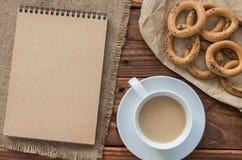 Τοπ εργασιακός χώρος γραφείων άποψης: Ardboard σημειωματάριο Ð ¡ με bagels και καφές στον ξύλινο πίνακα Στοκ Φωτογραφία