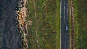 Τοπ κηφήνας άποψης που ακολουθεί το μαύρο αυτοκίνητο που κινείται κατά μήκος του δρόμου κόλπων φθινοπώρου πολύ κοντά προς την όμο απόθεμα βίντεο