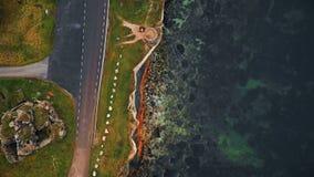 Τοπ κηφήνας άποψης που πετά κατά μήκος του όμορφου οδικού δικαιώματος αμμοχάλικου πέρα από τη διαβρωμένη ακτή της θάλασσας της Βα απόθεμα βίντεο