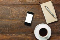 Τοπ κινητό τηλέφωνο γραφείων γραφείων άποψης, καφές, σημειωματάριο σε ξύλινο Στοκ φωτογραφία με δικαίωμα ελεύθερης χρήσης