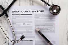 τοπ μορφή αξίωσης τραυματισμών εργασίας άποψης με το στηθοσκόπιο ιατρικό και την ασφαλιστική έννοια στοκ εικόνες