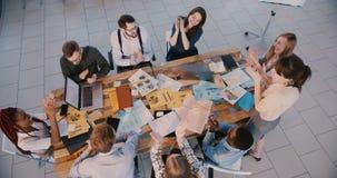 Τοπ ομάδα άποψης ευτυχών επιχειρηματιών που εργάζονται μαζί στο σύγχρ φιλμ μικρού μήκους