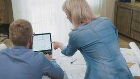 Τοπ ομάδα αρχιτεκτονικής άποψης που εργάζεται μαζί στο lap-top με τα σχεδιαγράμματα απόθεμα βίντεο