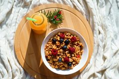 Τοπ οριζόντια άποψη σχετικά με τα υγιή μούρα granola προγευμάτων στο άσπρο κύπελλο και το φρέσκο πορτοκάλι juce στο στρογγυλό ξύλ στοκ εικόνες με δικαίωμα ελεύθερης χρήσης