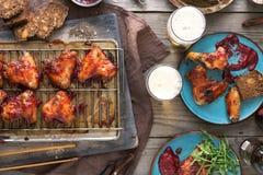Τοπ πίνακας γευμάτων άποψης με τα φτερά και την μπύρα κοτόπουλου Στοκ φωτογραφία με δικαίωμα ελεύθερης χρήσης