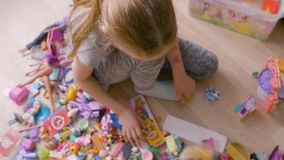 Τοπ παιχνίδι μικρών κοριτσιών άποψης με τη συνεδρίαση παιχνιδιών στο πάτωμα στο δωμάτιο Άποψη γύρω απόθεμα βίντεο