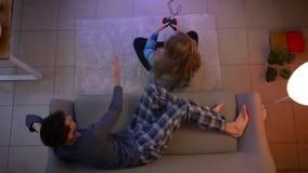 Τοπ πυροβολισμός του κοριτσιού videogame παιχνιδιού πιτζαμάτων και μια χαλάρωση τύπων στον καναπέ στο καθιστικό απόθεμα βίντεο