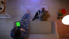 Τοπ πυροβολισμός του κοριτσιού videogame παιχνιδιού πιτζαμάτων με την προσοχή πηδαλίων και τύπων στην ταμπλέτα και να κουνήσει στ φιλμ μικρού μήκους
