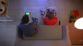 Τοπ πυροβολισμός των φίλων videogame παιχνιδιού πιτζαμάτων με το πηδάλιο και προσοχή στο smartphone στο καθιστικό απόθεμα βίντεο