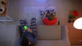 Τοπ πυροβολισμός των φίλων videogame παιχνιδιού πιτζαμάτων με το πηδάλιο και εργασία με το smartphone στο καθιστικό απόθεμα βίντεο