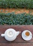 Τοπ πυροβολισμός - φλυτζάνι του τσαγιού και teakettle στον ξύλινο φραγμό στοκ εικόνες