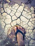 Τοπ πόδι άποψης του ατόμου και της παντόφλας στο ξηρό εδαφολογικό υπόβαθρο ρωγμών στοκ εικόνα