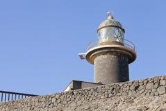 Τοπ πύργος φάρων γυαλιού στον γκρίζο τοίχο πετρών, Jandia, Κανάρια νησιά Στοκ εικόνα με δικαίωμα ελεύθερης χρήσης